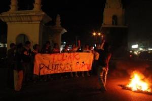 "Beberapa mahasiswa Unsyiah sedang melakukan orasi dengan membentangkan spanduk ""Tolak Politisasi Kampus"" dan membakar ban bekas di Simpang Galon, Kopelma Darussalam, Rabu (28/12/2011) malam. (Foto: Mirza/DETaK)"